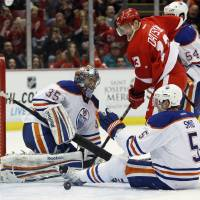 Photo - Detroit Red Wings center Pavel Datsyuk (13), of Russia, watches the puck bounce out of the net after scoring against Edmonton Oilers goalie Nikolai Khabibulin (35), of Russia, and defenseman Ladislav Smid (5), of Czechoslovakia, in the second period of an NHL hockey game Saturday, Feb. 9, 2013, in Detroit. (AP Photo/Duane Burleson)