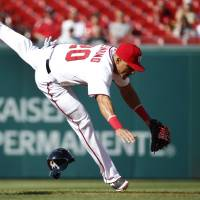 Photo - Washington Nationals shortstop Ian Desmond tries to keep his balance after missing the tag at second base as Miami Marlins Christian Yelich steals the base during the first inning of a baseball game at Nationals Park, Thursday, April 10, 2014, in Washington. (AP Photo/Alex Brandon)