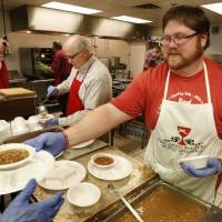 Photo - Harold Jones, left, and Chris Fourcade dish up beans Tuesday at the annual Benefit Bean Dinner sponsored by the Christian Men's Fellowship of First Christian Church. PHOTOs BY STEVE SISNEY, THE OKLAHOMAN