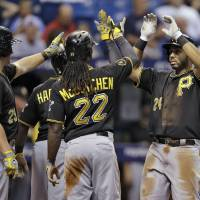 Photo - Pittsburgh Pirates' Pedro Alvarez (24) high fives teammates, including Andrew McCutchen (22) and Travis Snider (23) after hitting a three-run home run off Tampa Bay Rays starting pitcher Alex Cobb during the third inning of an interleague baseball game, Monday, June 23, 2014, in St. Petersburg, Fla. (AP Photo/Chris O'Meara)