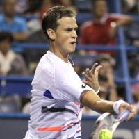 Photo - Vasek Pospisil, of Canada, returns the ball to Berdych, of the Czech Republic, at the Citi Open tennis tournament, Thursday, July 31, 2014, in Washington. (AP Photo/Luis M. Alvarez)
