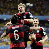 Photo - Germany's Toni Kroos (18) celebrates with Sami Khedira (6) and Miroslav Klose, right, after scoring his side's fourth goal during the World Cup semifinal soccer match between Brazil and Germany at the Mineirao Stadium in Belo Horizonte, Brazil, Tuesday, July 8, 2014. (AP Photo/Natacha Pisarenko)