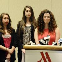 Photo - University of Connecticut student Rosemary Richi, at podium, answers questions from the media as attorney Gloria Allred, right, Kylie Angell, left, Erica Daniels, second from left, and Carolyn Luby, look on, during a news conference, Friday, July 18, 2014. The University of Connecticut will pay nearly $1.3 million to settle a federal lawsuit filed by five women who claimed the school responded to their sexual assault complaints with indifference, the two sides announced Friday.  (AP Photo/Jessica Hill)
