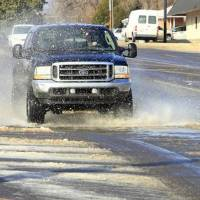 Photo - Vehicles try to navigate through ice and water from a water main break at the intersection of NW 50 Street and Portland Ave. in Oklahoma City Tuesday, Feb. 11, 2014. Photo by Paul B. Southerland, The Oklahoman