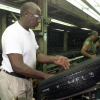 Photo - Jessie Broussard inspects a tire at Dayton Tire plant in Oklahoma City in 2000.  - PHOTO BY STEVE GOOCH, THE OKLAHOMAN