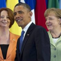 Photo -   President Barack Obama, center, takes his place with other leaders, including Australian Prime Minister Julia Gillard, left, and German Chancellor Angela Merkel, for the Family Photo during the G20 Summit, Monday, June 18, 2012, in Los Cabos, Mexico. (AP Photo/Carolyn Kaster)