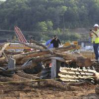 Photo - Investigators look over the scene of a double fatality accident Monday, June 2, 2014, in Clinton, Ark. Officials said a log truck lost control and slid onto a bridge under construction killing two and injuring more than 20 workers on the bridge. (AP Photo/Arkansas Democrat-Gazette, Staton Breidenthal)