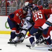 Photo - Washington Capitals defenseman Dmitry Orlov (81), from Russia, left wing Jason Chimera (25) and others combine on San Jose Sharks center Andrew Desjardins (10) in front of the goal, during the second period of an NHL hockey game, Tuesday, Jan. 14, 2014, in Washington. (AP Photo/Alex Brandon)