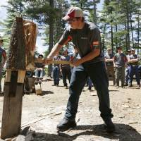 Photo - In this July 10, 2014 photo, Tommy Grunow of Riverside, Conn., peels the bark from a white pine log at the Adirondack Woodsmen's School at Paul Smith's College in Paul Smiths, N.Y. Eighteen young students in matching gray sports shirts took part recently in a weeklong crash course on old-school lumberjack skills such as sawing, chopping, ax throwing, log boom running and pole climbing. (AP Photo/Mike Groll)