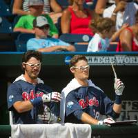 Photo - Mississippi's Evan Anderson, left, and Brantley Bell dress up like Harry Potter late in an NCAA College World Series baseball game against Virginia in Omaha, Neb., Saturday, June 21, 2014. (AP Photo/The World-Herald, Brendan Sullivan) MAGS OUT, TV OUT