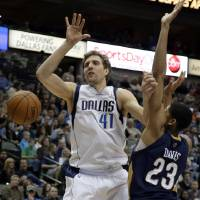 Photo - Dallas Mavericks power forward Dirk Nowitzki (41) loses control of the ball after being fouled by New Orleans Pelicans' Anthony Davis (23) on a shot attempt in the first half of an NBA basketball game, Saturday, Jan. 11, 2014, in Dallas. (AP Photo/Tony Gutierrez)