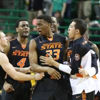 Photo - OSU players surround Leyton Hammonds, center, after he hit a shot sending the game against Baylor to overtime on Monday in Waco, Texas. Baylor won 70-64. AP Photo
