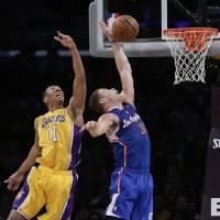 Photo - Los Angeles Clippers' Blake Griffin, center, goes up for a basket against Los Angeles Lakers' Wesley Johnson during the first half of an NBA basketball game on Thursday, March 6, 2014, in Los Angeles. (AP Photo/Jae C. Hong)