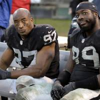 Photo - Oakland Raiders defensive end Andre Carter (97) and defensive end Lamarr Houston (99) sit on the bench during the fourth quarter of an NFL football game against the Cleveland Browns in Oakland, Calif., Sunday, Dec. 2, 2012. The Browns won 20-17. (AP Photo/Tony Avelar)