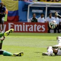 Photo - Colombia's Teofilo Gutierrez, right, tries to kick the ball while on the ground during the group C World Cup soccer match between Colombia and Ivory Coast at the Estadio Nacional in Brasilia, Brazil, Thursday, June 19, 2014.  (AP Photo/Sergei Grits)