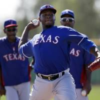 Photo - Texas Rangers' Neftali Feliz throws during batting practice as manager Ron Washington, left, and Darren Oliver, right rear, watch during spring training baseball practice, Monday, Feb. 17, 2014, in Surprise, Ariz. (AP Photo/Tony Gutierrez)