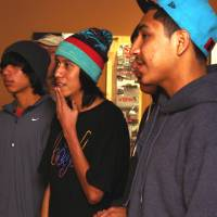 Photo - From left, Jorge Yeahqo (Kiowa),  Quincy Thompson (Zuni)  and Patrick Solomon (Choctaw),  all students at the Riverside Indian School in Anadarko, recognize some of their favorite skaters in a photograph included in the