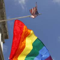 Photo - In this file photo from Thursday, Aug. 12, 2010, a rainbow flag flies below the American flag outside City Hall in San Francisco. The U.S. Supreme Court decided Friday, Dec. 7, 2012, to hear the appeal of a ruling that struck down Proposition 8, the state's measure that banned same sex marriages. The highly anticipated decision by the court means same-sex marriages will not resume in California any time soon. The justices likely will not issue a ruling until spring of next year. A federal appeals court ruled in February that Proposition 8's ban on same-sex marriage was unconstitutional. But the court delayed implementing the order until same-sex marriage opponents proponents could ask the U.S. Supreme Court to review the ruling. (AP Photo/Ben Margot)