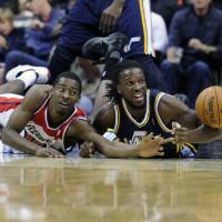 Photo -   Washington Wizards' Jordan Crawford, left, fights for the ball against Utah Jazz's DeMarre Carroll, right, during the first half of an NBA basketball game, Saturday, Nov. 17, 2012, in Washington. (AP Photo/Nick Wass)