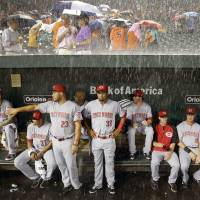 Photo - Members of the Cincinnati Reds watch from the dugout as heavy rain falls during a rain delay in the first inning of an interleague baseball game against the Baltimore Orioles, Tuesday, Sept. 2, 2014, in Baltimore. (AP Photo/Patrick Semansky)