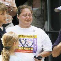 Photo - Tammy Smith cries as she speaks with OSBI agent Ben Rosser after the press conference at the Okfuskee County Courthouse, Thursday, June 12, 2008. Tammy is the cheerleader sponsor for Taylor and Skyla's squad and her son Bryan, 13, at right, is a classmate of the girls. Photo by David McDaniel