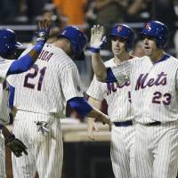 Photo - New York Mets' Taylor Teagarden (23) celebrates with David Wright (5), Lucas Duda (21) and Curtis Granderson after hitting a grand slam home run during the sixth inning of a baseball game against the Milwaukee Brewers, Tuesday, June 10, 2014, in New York. (AP Photo/Frank Franklin II)