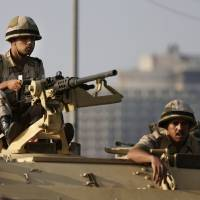 Photo - Egyptian army soldiers take their positions on top of their armored vehicle to guard the entrances of Tahrir square, in Cairo, Egypt, Monday, July 8, 2013. Egyptian military officials said gunmen killed at least five supporters of the former president when people tried to storm a military building in Cairo. The official, who declined to be named because he was not authorized to brief reporters, also said a group had tried to storm the headquarters of the Republican Guard. He added that those killed had been supporters of former President Mohammed Morsi camped outside the building in protest at his overthrow. (AP Photo/Hassan Ammar)