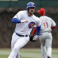 Photo - Chicago Cubs' Ryan Kalish runs to third after hitting a triple during the first inning of a baseball game scoring Emilio Bonifacio against the Philadelphia Phillies in Chicago, Sunday, April 6, 2014. (AP Photo/Nam Y. Huh)