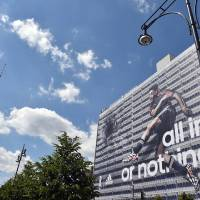 Photo - German national soccer player Mesut Ozil  is visible  on the facade of a publisher's building at Alexanderplatz  square inBerlin, Germany, Friday June 6, e 2014. Sportswear manufacturer Adidas has put up the advertisement on the entire facade of the building prior to the soccer World Cup  tournament  in Brazil. (AP Photo/dpa,Jens Kalaene)