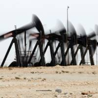 Photo - A row of oil pumps work in the desert oil fields of Sakhir, Bahrain.                     AP File Photo