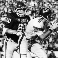 Photo - RICKY BRYAN / BEDLAM: University of Oklahoma defenseman Rick Bryan (80) closes in on Oklahoma State University quarterback John Doerner (5) during game action in Norman.  The Sooners smothered the Cowboys, 63-14. Staff photo by Jim Argo taken 11/29/80. File:  College Football/OU/OU-OSU/Rick Bryan/1980