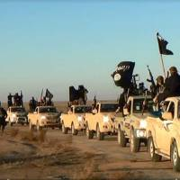 Photo - This image posted on a militant website on Tuesday, Jan. 7, 2014, which is consistent with AP reporting, shows a convoy of vehicles and fighters from the al-Qaida linked Islamic State of Iraq and the Levant (ISIL) fighters in Iraq's Anbar Province. With al-Qaida linked fighters and allied tribal gunmen camped on the outskirts, a tentative calm took hold over Fallujah on Friday, Jan. 10, 2014 and residents started to return to the besieged city west of Baghdad. Government forces were stationed nearby as sporadic street fighting breaks out in other cities. The picture painted by residents, officials and international groups suggests that both the militants and government forces are preparing for a long standoff with civilians caught in the middle.(AP Photo via militant website)