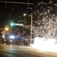 Photo - A device deployed by police goes off in the street as police and protesters clash Wednesday, Aug. 13, 2014, in Ferguson, Mo. Authorities in the St. Louis suburb where an unarmed black teen was shot and killed by a police officer have used tear gas to try to disperse protesters after flaming projectiles were thrown from the crowd. (AP Photo/Jeff Roberson)