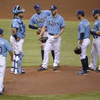 Photo - Tampa Bay Rays manager Joe Maddon (70) walks to the mound to take out starting pitcher Erik Bedard, center, during the sixth inning of a baseball game against the Houston Astros in St. Petersburg, Fla., Sunday, June 22, 2014. (AP Photo/Phelan M. Ebenhack)