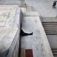 Photo - A homeless man sits near the closed entrance of a Metro station in central Syntagma square during a strike held by the unions of metro services in Athens, Tuesday, Jan. 22, 2013. Striking subway workers in Athens defied a court order to return to work and continued their protest for a sixth day on Tuesday, as demonstrations against new pay cuts escalated in the Greek capital. (AP Photo/Petros Giannakouris)