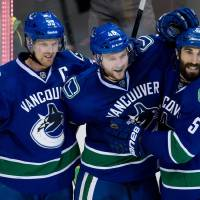 Photo - Vancouver Canucks' Henrik Sedin, of Sweden, from left to right, Nicklas Jensen, of Denmark, and Jason Garrison celebrate Jensen's goal against the Nashville Predators during third period NHL hockey action in Vancouver, British Columbia, on Wednesday, March 19, 2014. (AP Photo/The Canadian Press, Darryl Dyck)