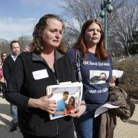 Photo - Cherie Sharkey, left, weeps for her son Michael Sharkey who died in his used 2006 Chevy Cobalt in Dresden, NY, as she walks with Laura Christian, of Harwood, Md., birth mother of Amber Marie Rose, the first reported victim of the General Motors safety defect, on Capitol Hill in Washington, Tuesday, April 1, 2014, to represent their children at a news conference. The House Energy and Commerce Subcommittee on Oversight and Investigations will look for answers today from GM CEO Mary Barra about a faulty ignition switch and mishandled recall of 2.6 million cars that's been linked to 13 deaths and dozens of crashes. (AP Photo/J. Scott Applewhite)