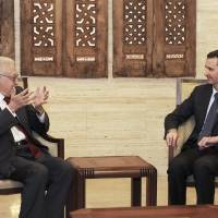 Photo -   In this photo released by the Syrian official news agency SANA, Syrian President Bashar Assad, right, meets with the U.N.-Arab League envoy Lakhdar Brahimi, left, in Damascus, Syria, Saturday, Sept. 15, 2012. The new international envoy tasked with ending Syria's civil war says the country's conflict is a threat to world peace. (AP Photo/SANA)