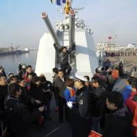 Photo - In this Wednesday Dec. 26, 2012, a man, center in back, poses for a photo while others visit Chinese navy's missile destroyer Qingdao on the destroyer's public open day in Qingdao, in eastern China's Shandong province. (AP Photo)  CHINA OUT