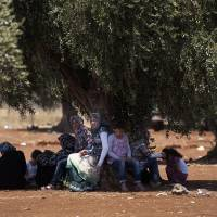 Photo -   In this Wednesday, Aug. 15, 2012 photo, a Syrian refugee family sit under a tree by the border with Turkey after they left their home, in the town of Azaz on the outskirts of Aleppo, Syria. Thousands of Syrians who have been displaced by the country's civil are struggling to find safe shelter while shelling and airstrikes by government forces continue. (AP Photo/ Khalil Hamra)