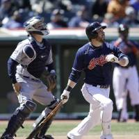 Photo - Cleveland Indians' Jason Kipnis, right, watches his ball after hitting a two-run home run off San Diego Padres starting pitcher Eric Stults during the sixth inning in the first game of a baseball doubleheader, Wednesday, April 9, 2014, in Cleveland. (AP Photo/Tony Dejak)