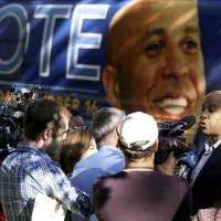 Photo - Newark Mayor Cory Booker, right, talks to reporters near his tour bus while visiting supporters at a senior center, Tuesday, Oct. 15, 2013, in Newark, N.J. Booker will be going up against his Republican opponent Steve Lonegan Wednesday, Oct. 16, during a special election to fill New Jersey's vacant seat in the U.S. Senate. (AP Photo/Julio Cortez)