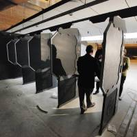 Photo -  Above: Wilshire Gun general manger Jeff Swanson is silhouetted in one of the shooting stalls under construction.    PAUL B. SOUTHERLAND -  PAUL B. SOUTHERLAND
