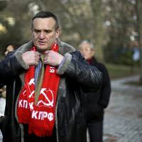 Photo - Igor Vasiliyev, head of the local branch of the Communist Party, adjusts his scarf decorated with a hammer and sickle, a symbol of the communist movement, as he leads a protest in the 50 Years of Victory in the Great Patriotic War Park to hold the first official demonstration in the designated Olympic protest area for the 2014 Winter Olympics, Saturday, Feb. 1, 2014, in Sochi, Russia. The protestors were members of the local branch of the Communist Party demonstrating for government benefits for Russian children of World War II born between 1928 and 1945. (AP Photo/David Goldman)