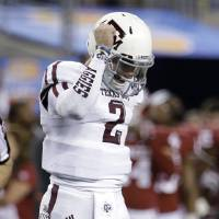 Photo - Texas A&M's Johnny Manziel celebrates a touchdown by Ben Malena in the second half of the Cotton Bowl NCAA college football game against Oklahoma on Friday, Jan. 4, 2013, in Arlington, Texas. (AP Photo/Tony Gutierrez)