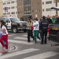 Photo - Officers escort witnesses to a bus at the Renown Regional Medical Center after a lone gunman shot and injured four people before killing himself , Tuesday, Dec. 17, 2013 in Reno, Nev. (AP Photo/Scott Sady)