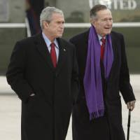 Photo - FILE - In this Dec. 26, 2008 file photo, President George W. Bush walks with his father, former President George H.W. Bush, at Andrews Air Force Base, Md. A criminal investigation is under way after a hacker apparently accessed private photos and emails sent between members of the Bush family, including both former presidents, according to reports Friday, Feb. 8, 2013. (AP Photo/Evan Vucci, File)