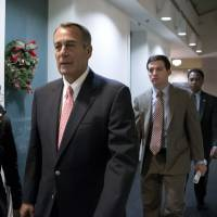 Photo - Speaker of the House John Boehner, R-Ohio, walks to a closed-door GOP caucus as Congress meets to negotiate a legislative path to avoid the so-called