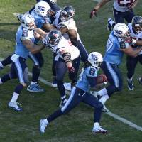 Photo - Tennessee Titans running back Chris Johnson (28) runs eleven yards for a touchdown against the Houston Texans in the third quarter of an NFL football game on Sunday, Dec. 29, 2013, in Nashville, Tenn. (AP Photo/Mark Zaleski)