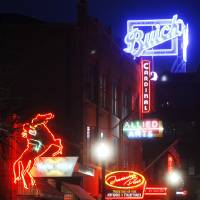 Photo - The new Buick sign Thursday at 1101 N Broadway in Automobile Alley is an addition to several other neon signs in the immediate vicinity. The Buick sign was lit for the first time at 8 p.m. in Oklahoma City. Photo by KT King, The Oklahoman   KT King -  The Oklahoman